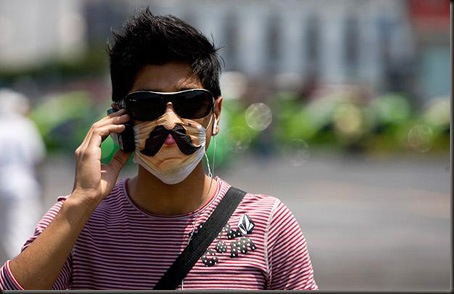 A man wears a decorated protective mask as he talks on his cell phone in downtown Mexico City, Monday, April 27, 2009.  A fatal strain of swine flu has been detected in Mexico while the virus has been confirmed or suspected in at least a half-dozen other countries.  (AP Photo/Eduardo Verdugo)